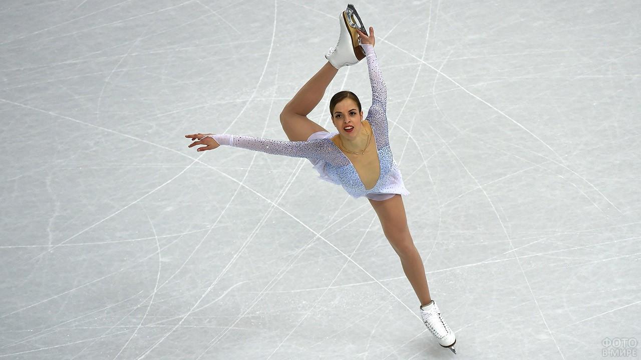 Изящная фигуристка в белом на льду