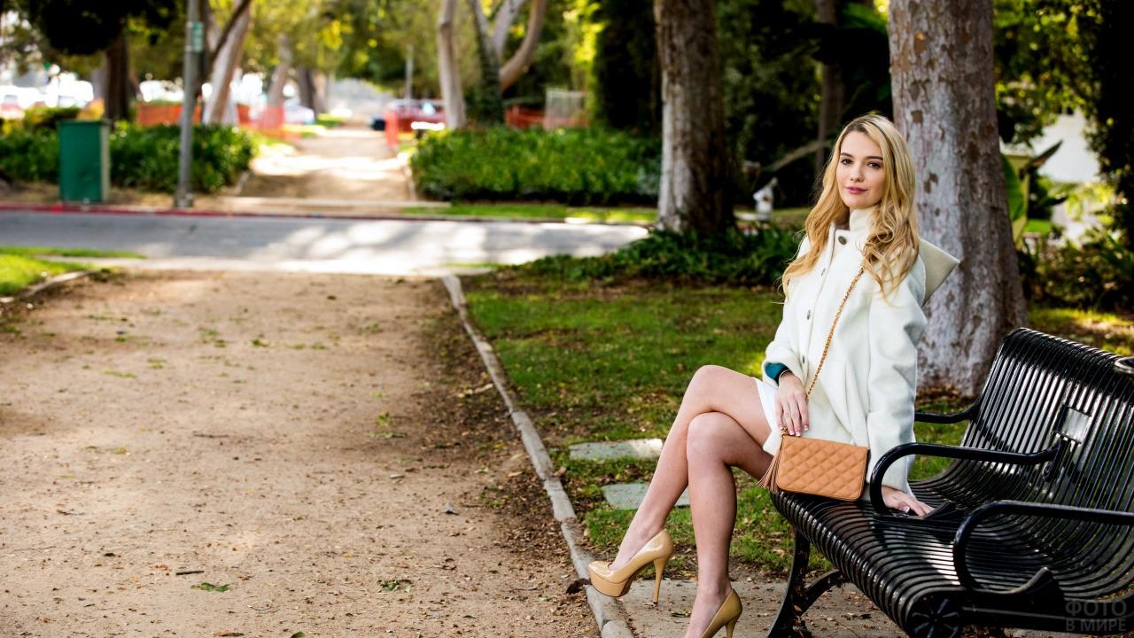 Блондинка сидит на лавочке