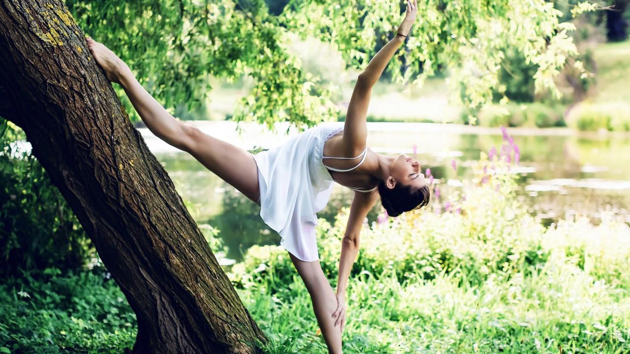 Девушка делает гимнастику на природе