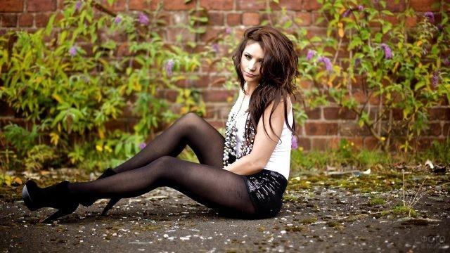 Девушка в колготках сидит на земле
