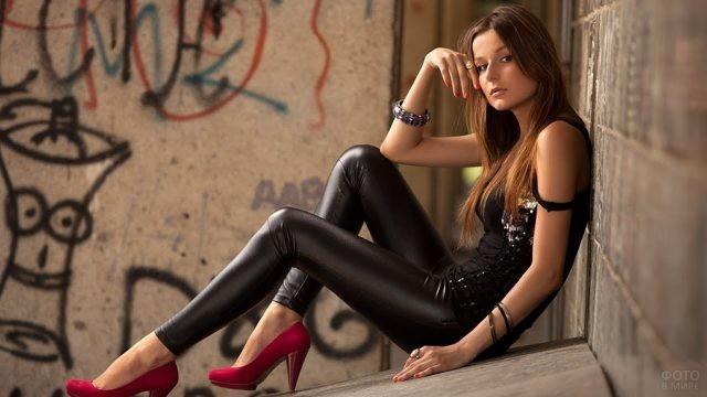 Девушка в красных туфлях и кожаных леггинсах