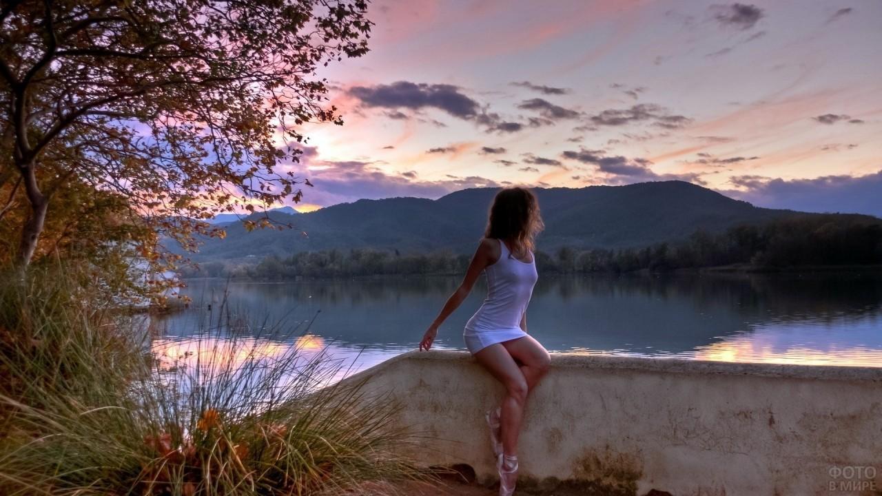 Девушка в пуантах сидит у воды