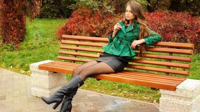 Длинноволосая девушка в мини юбке и сапогах сидит на лавочке