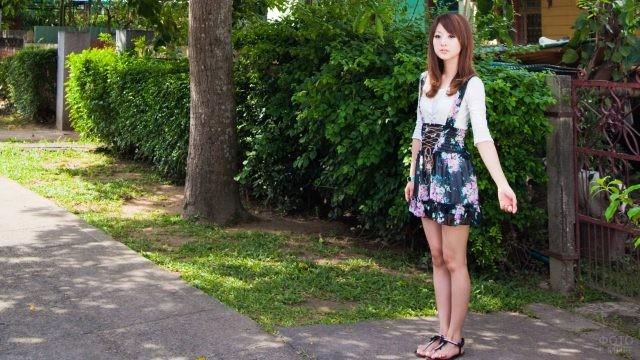Японская девушка стоит у калитки