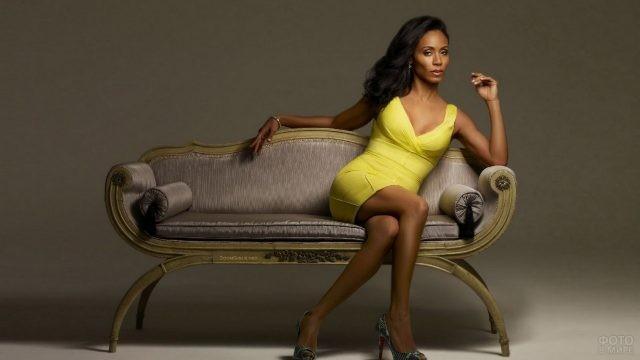 Мулатка в жёлтом платье сидит на диване