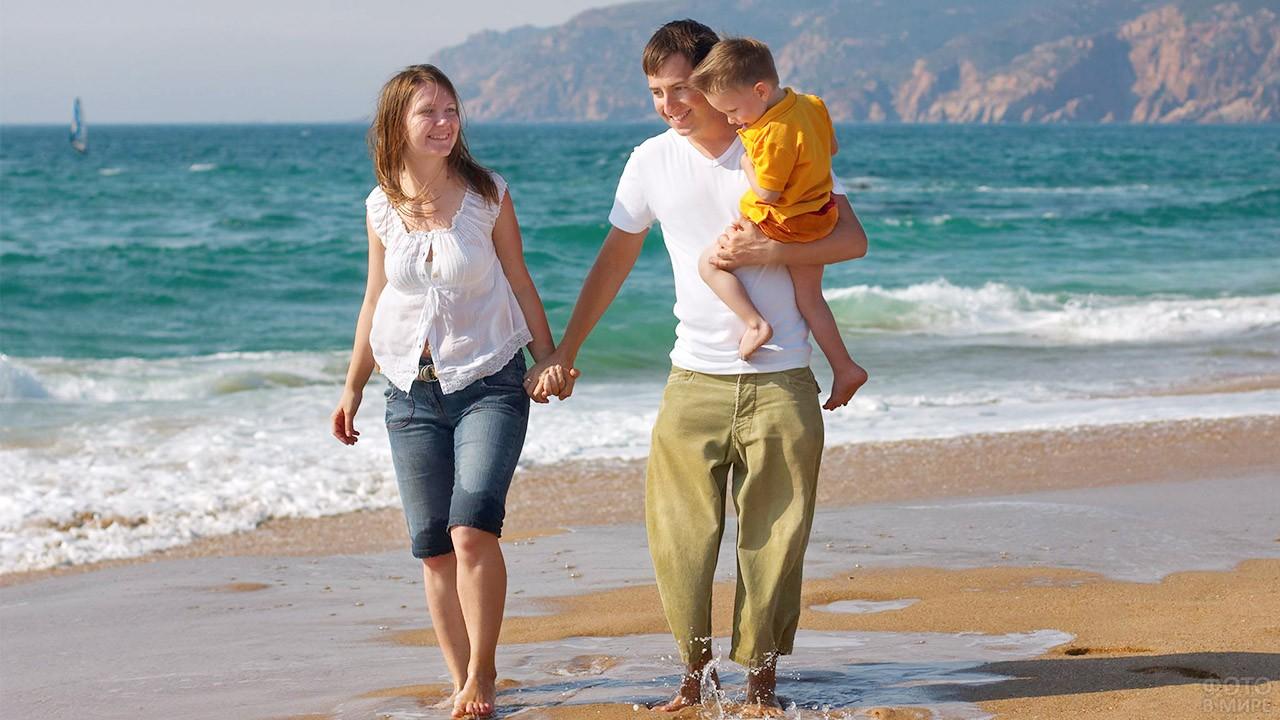 Молодая семья с маленьким сыном на пляже