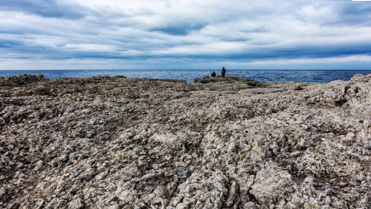 Рыбаки на разделяющем пляж мысе