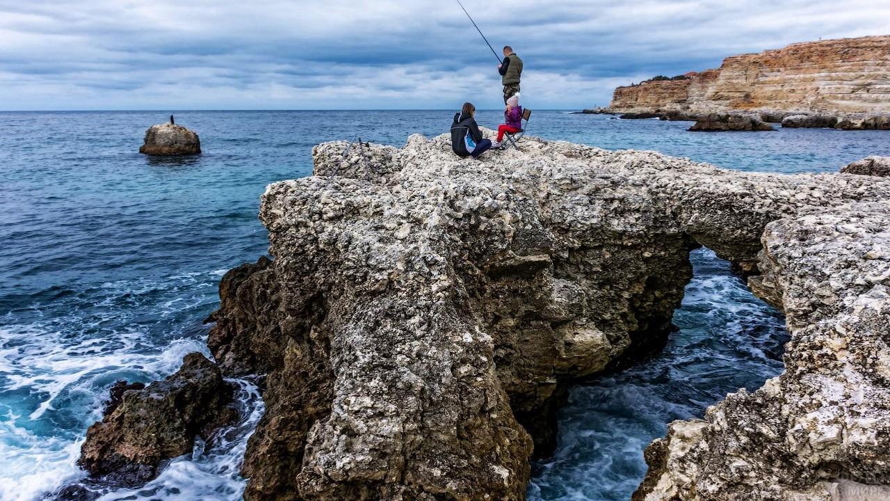Семейная рыбалка со скалы у пляжа