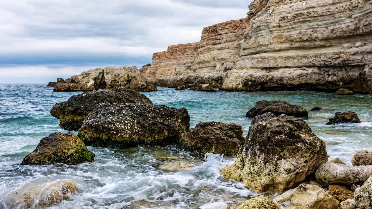 Валуны на мелководье дикой части пляжа