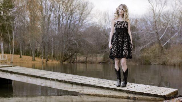 Блондинка в чёрном ажурном платье на мостике