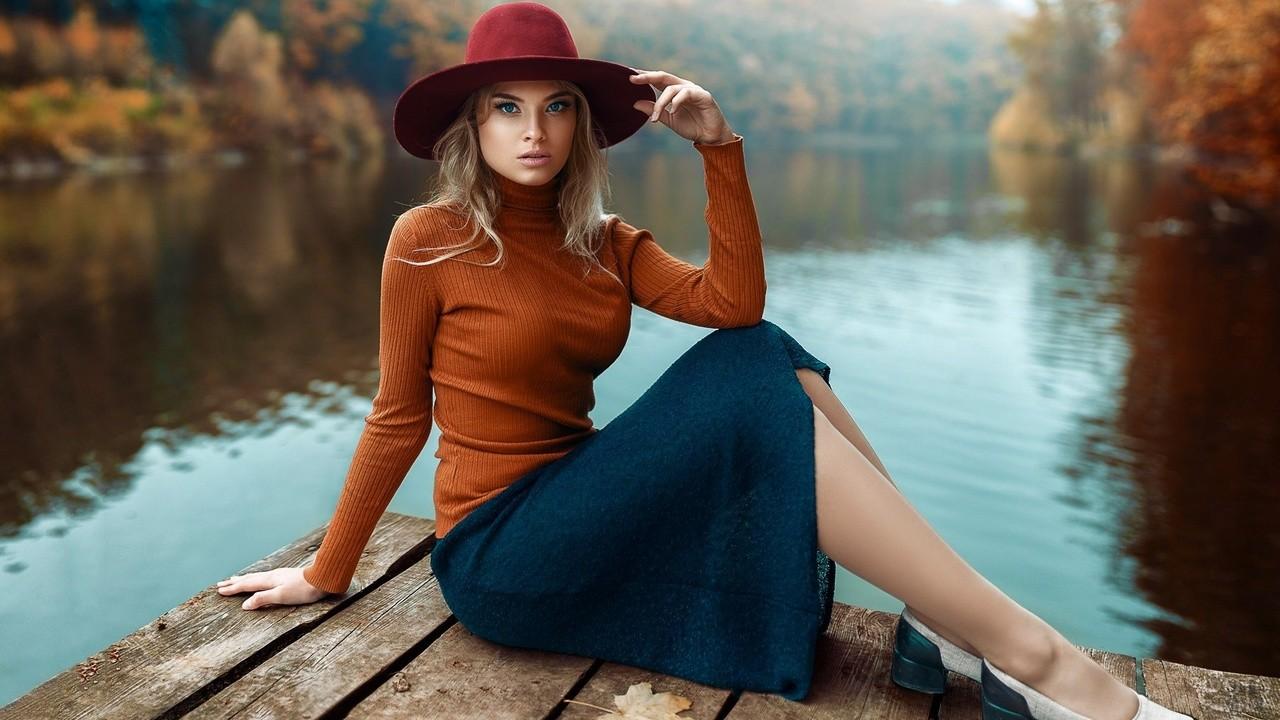 Девушка сидит на мостике в шляпе