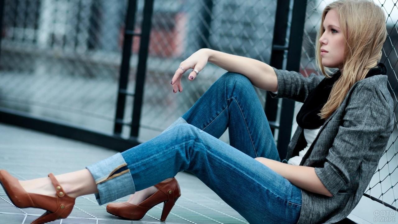 Девушка в джинсах сидит у забора