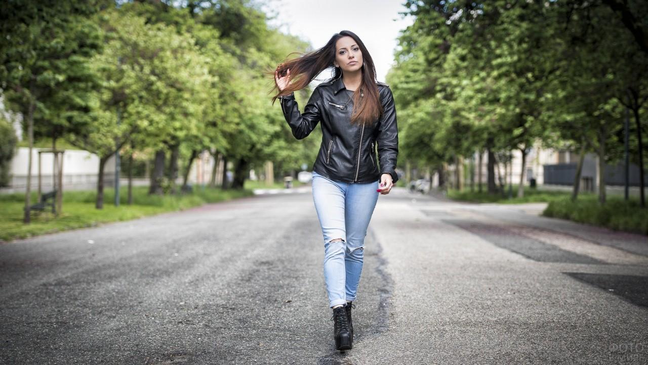 Девушка в кожаной куртке и рваных джинсах