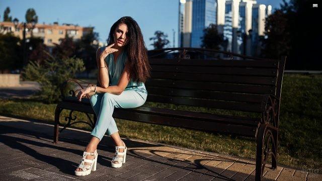 Длинноволосая девушка сидит на скамейке