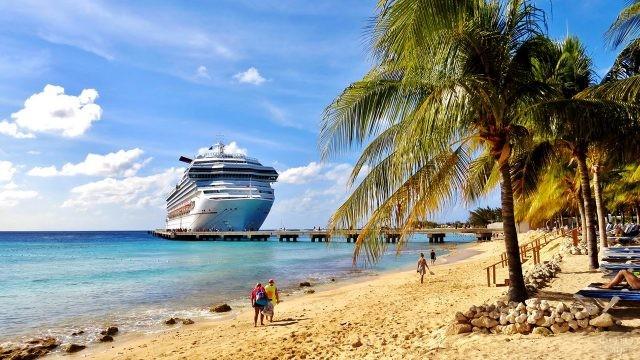Круизный лайнер возвышается над песчаным пляжем