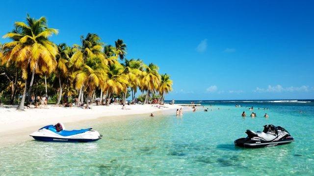 Туристы купаются на мелководье у острова Гваделупа