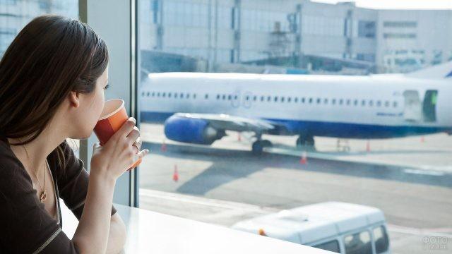 Девушка пьёт кофе, глядя на самолёт