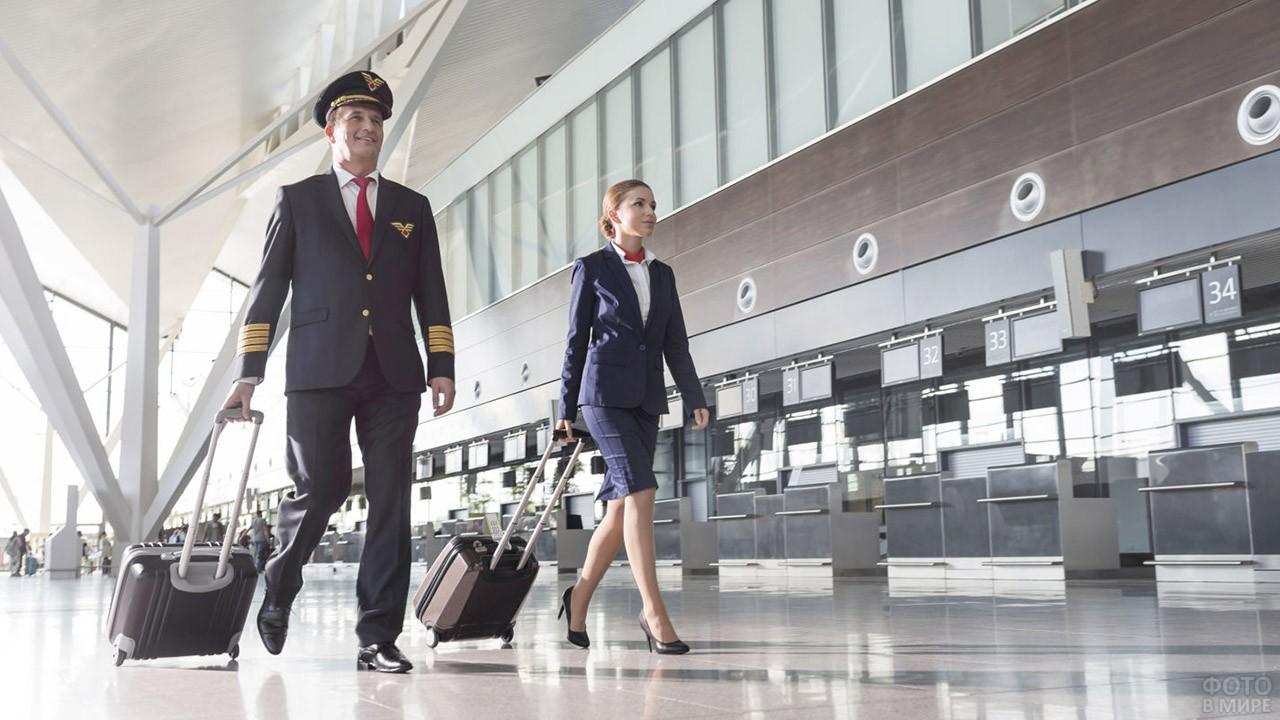 Пилот и стюардесса идут с чемоданами по залу
