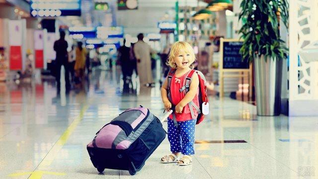 Счастливый малыш с чемоданами