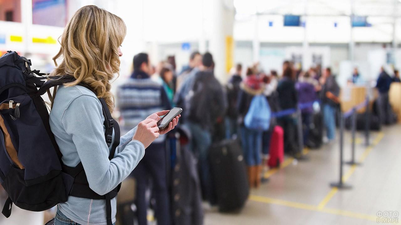 Туристка с рюкзаком и смартфоном стоит в очереди