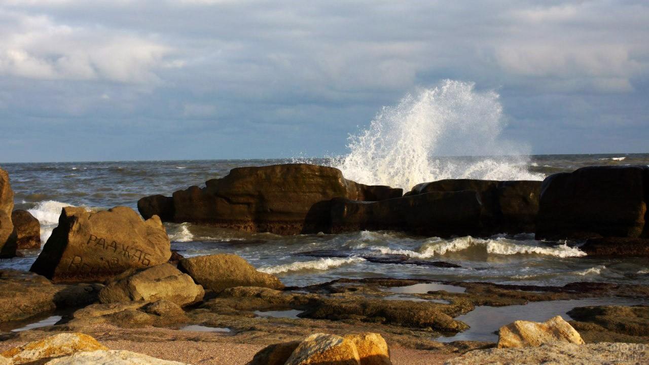Волна разбивается о прибрежные скалы