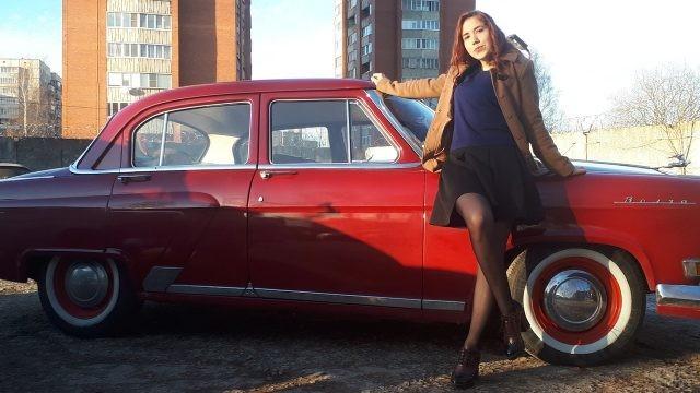 Девушка позирует рядом с советской Волгой