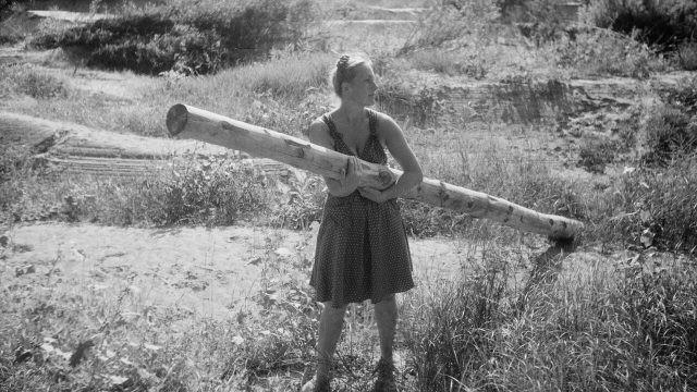 Девушка стоит с бревном