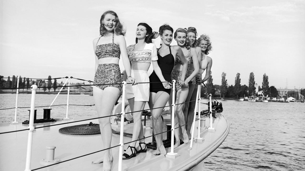 Девушки в купальниках стоят на палубе