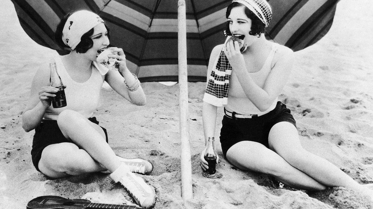 Две девушки сидят под зонтом