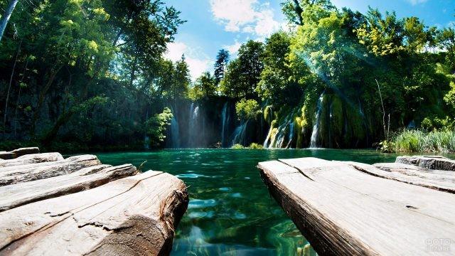 Деревянный помост над озером с видом на водопады
