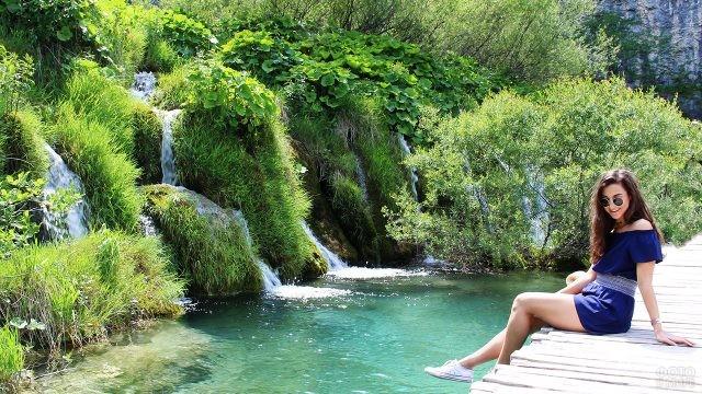 Девушка сидит на помосте над озером