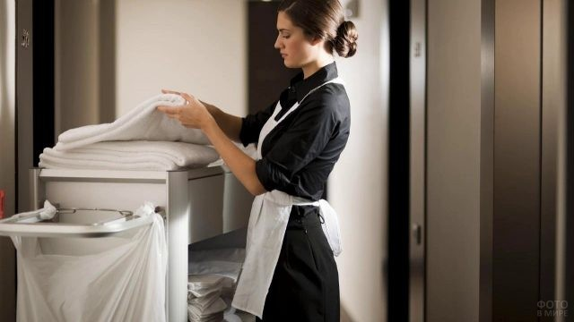 Горничная берёт полотенце
