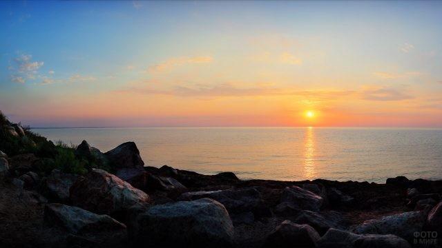 Закат над каменистым диким пляжем
