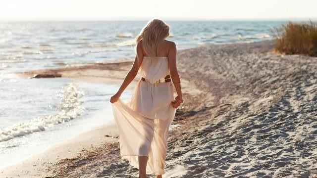 Блондинка в белом платье на побережье