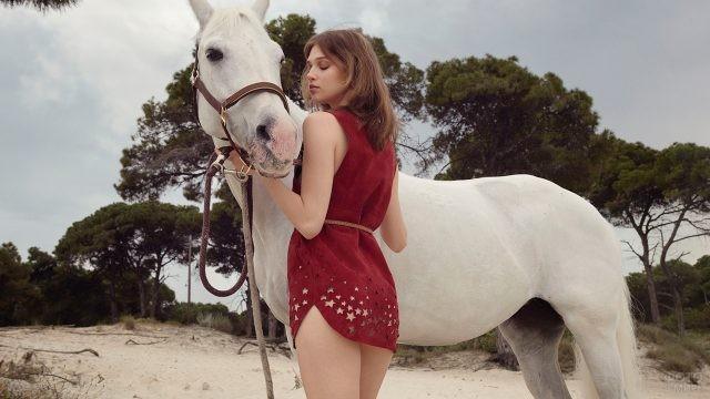 Девушка держит под уздцы белого коня
