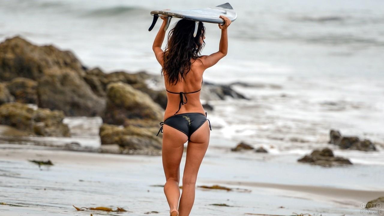 Девушка несёт доску для сёрфинга