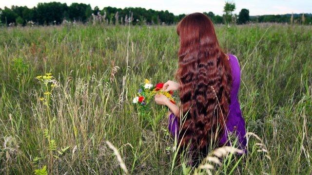 Девушка с длинными волосами плетёт венок