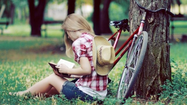 Девушка с книгой около велосипеда