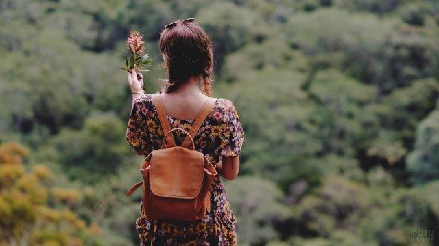 Девушка с рюкзаком держит цветок