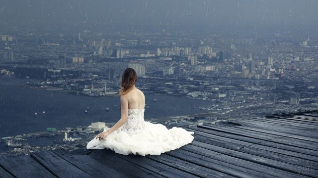 Девушка сидит на крыше во время дождя