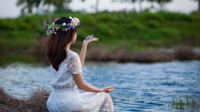 Девушка у реки с венком на голове