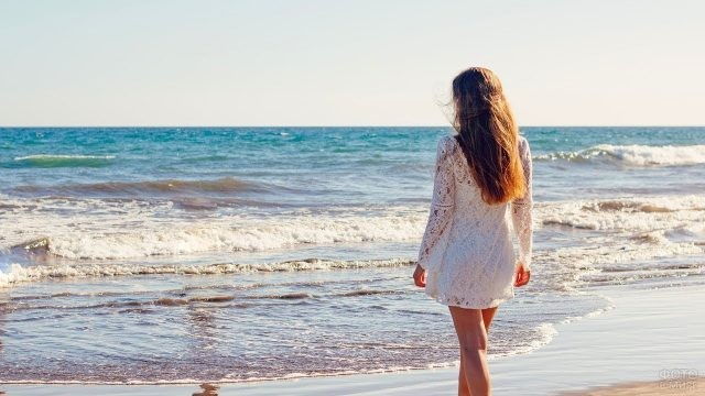 Девушка в белом ажурном платье у моря