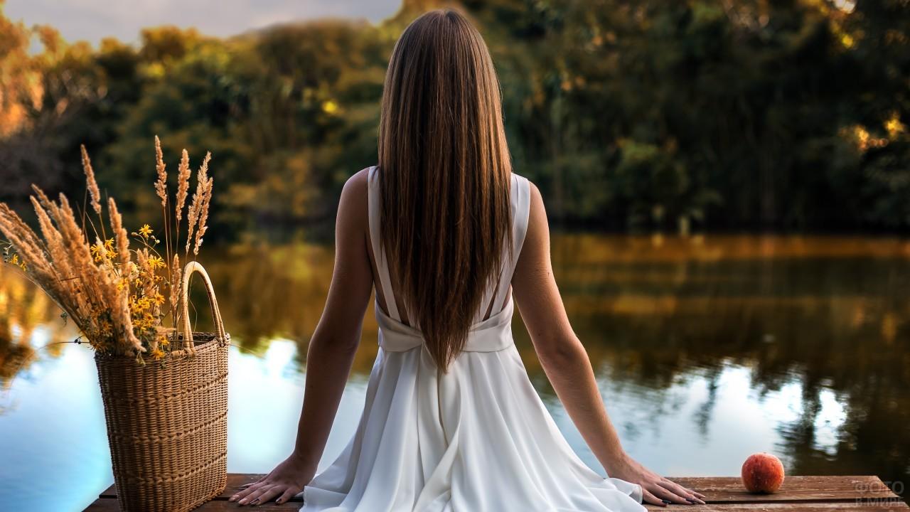 Девушка в белом платье сидит на мостике