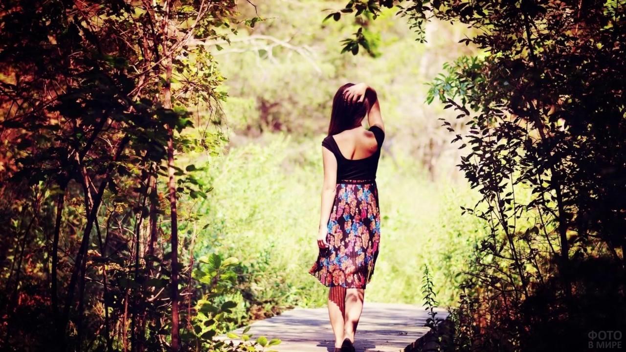 Девушка в цветастой юбке идёт по мостику