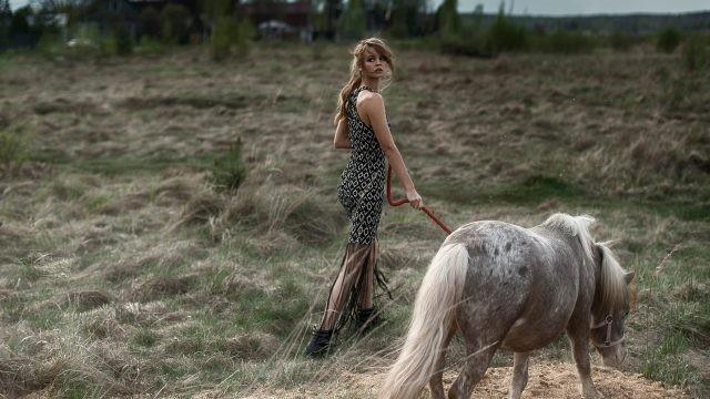 Девушка выгуливает пони