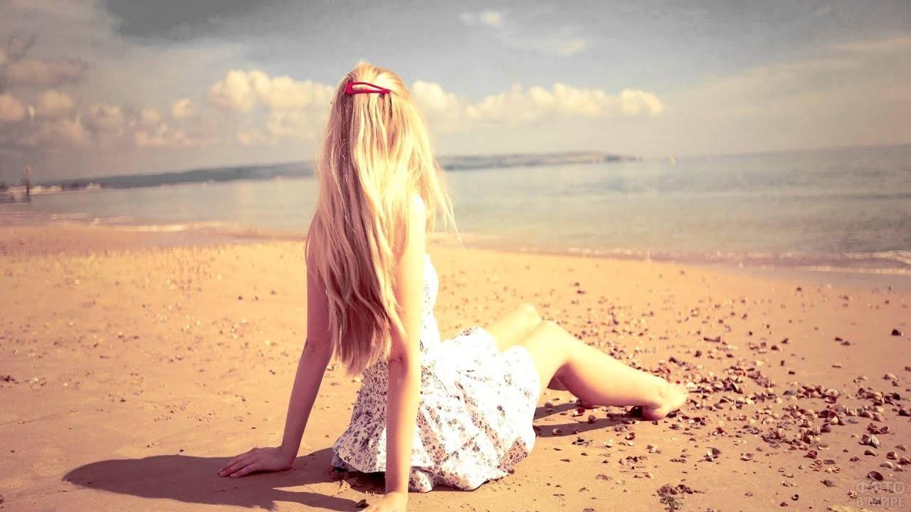 Белокурая девушка смотрит на море