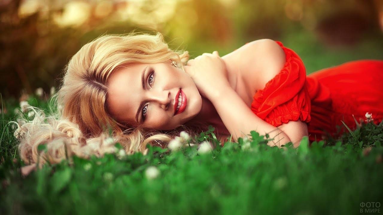 Блондинка в красном платье лежит на траве