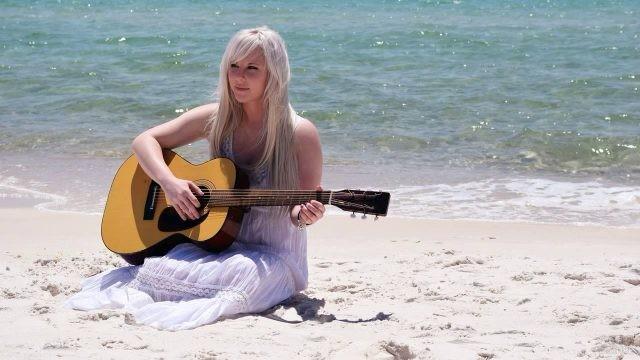 Девушка с гитарой на море