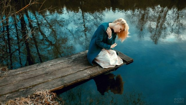 Девушка сидит у реки