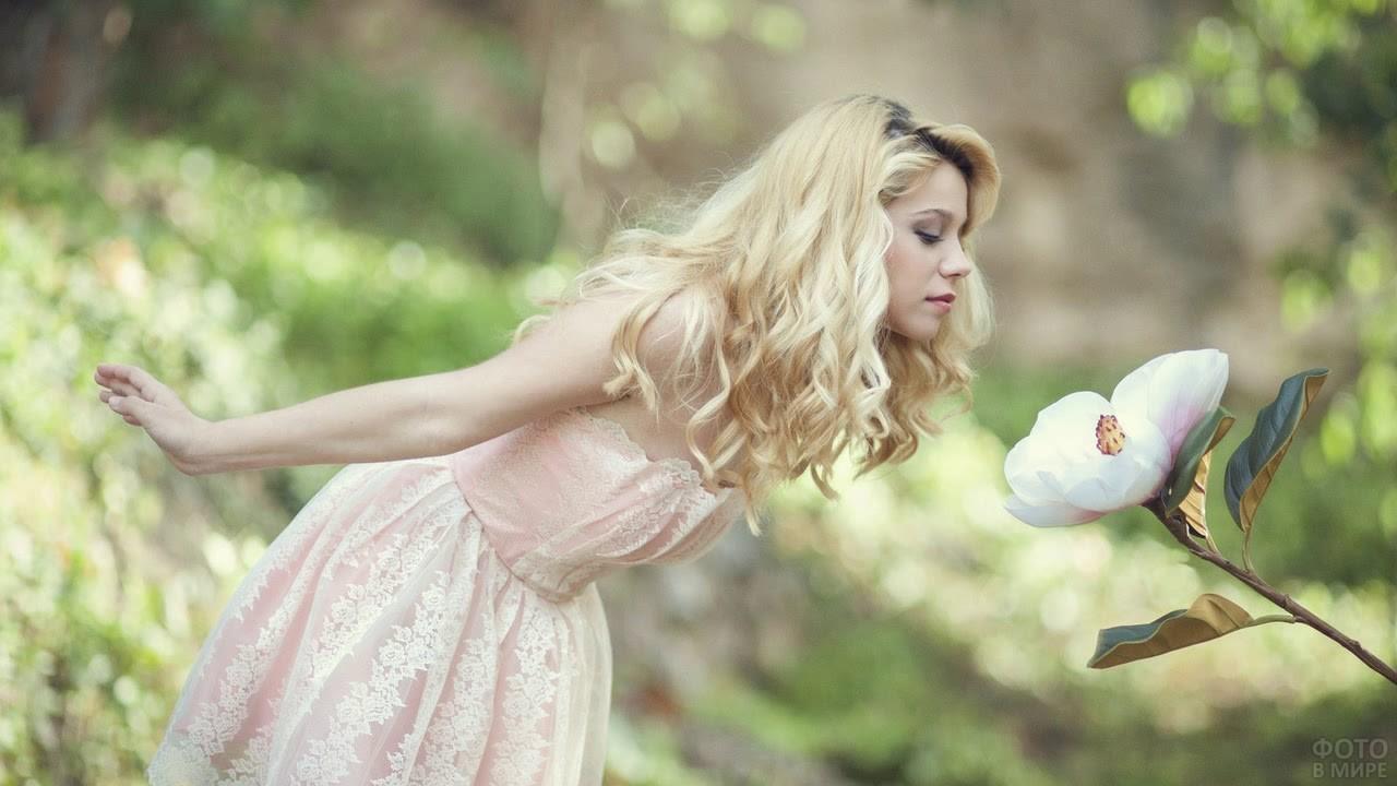 Девушка тянется к цветку